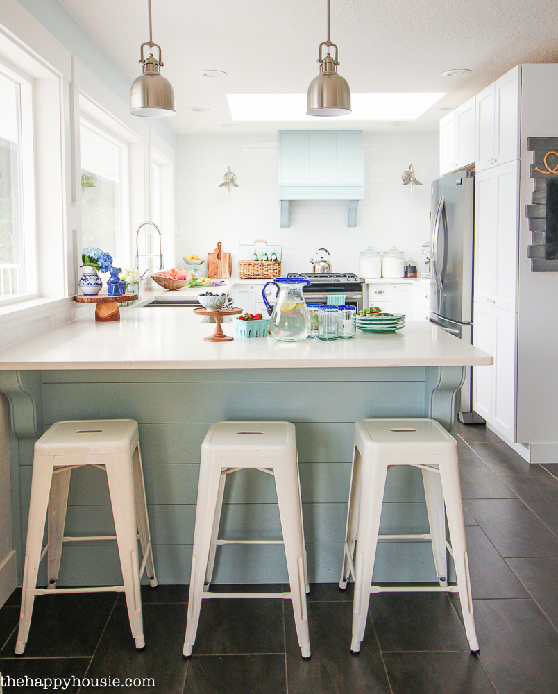 A cozy coastal cottage kitchen with classic white metal bar stools for the kitchen peninsula.