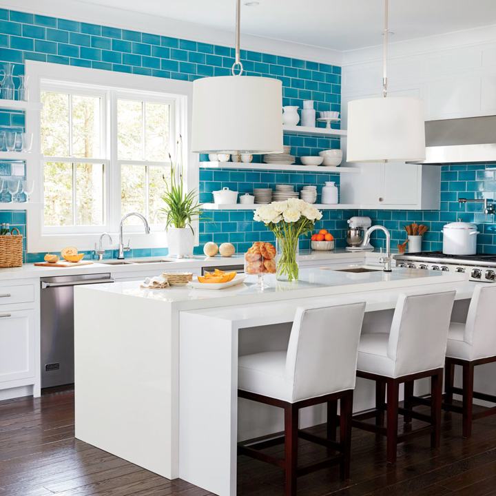 A dreamy kitchen design featuring turquoise tiles & white cabinetry. The white bar stools with wood legs  blend seamlessly with the white counter top and wood flooring.
