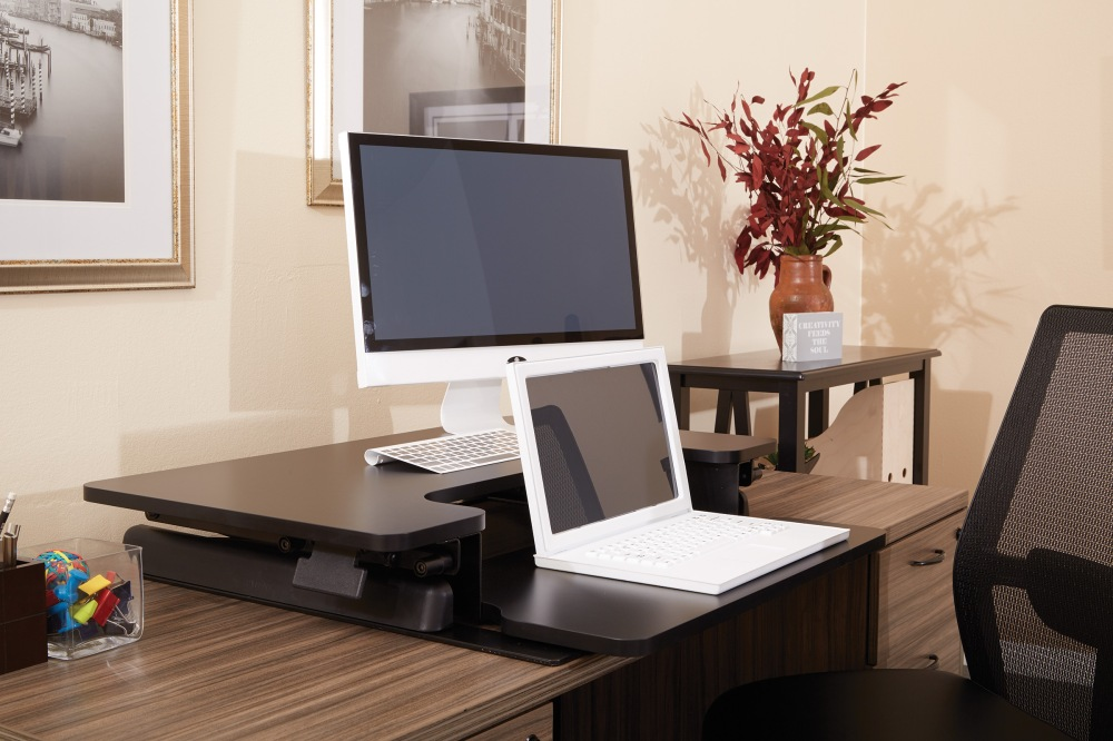 Love your current desk, but want to try a standing option the new OSP Designs Desk Riser rests on your desk top and adjusts up and down as needed.