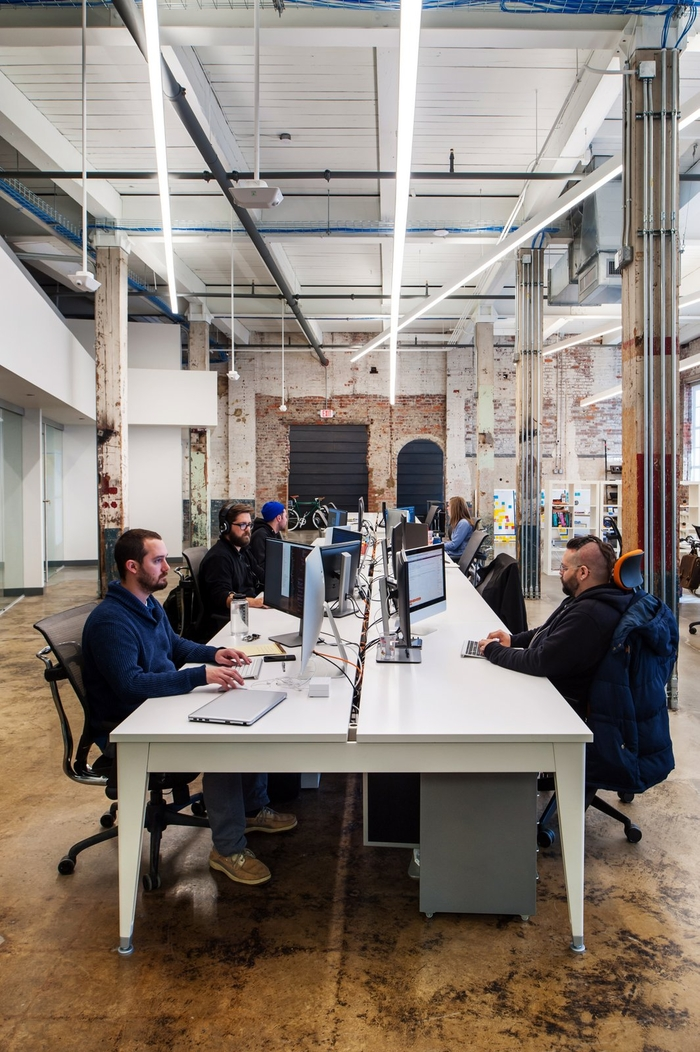 The CO+LAB office in Richmond, VA has shared desk space and an industrial feel typical of the modern open office.