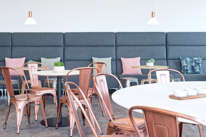 The playfully casual vibe at this London office features a cafe style break area featuring a variety of table sizes along with metal chairs and stools for people to gather for lunch, coffee breaks, or a casual meeting during the work day.